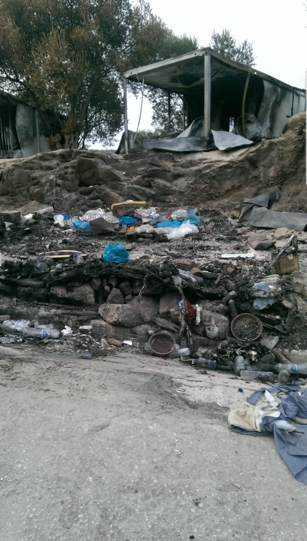 """1. Bild: ausgebrannter Container im """"Jungle"""" vor dem auch noch nach dem Brand das Ausmaß des Plastikproblems deutlich zu sehen ist."""
