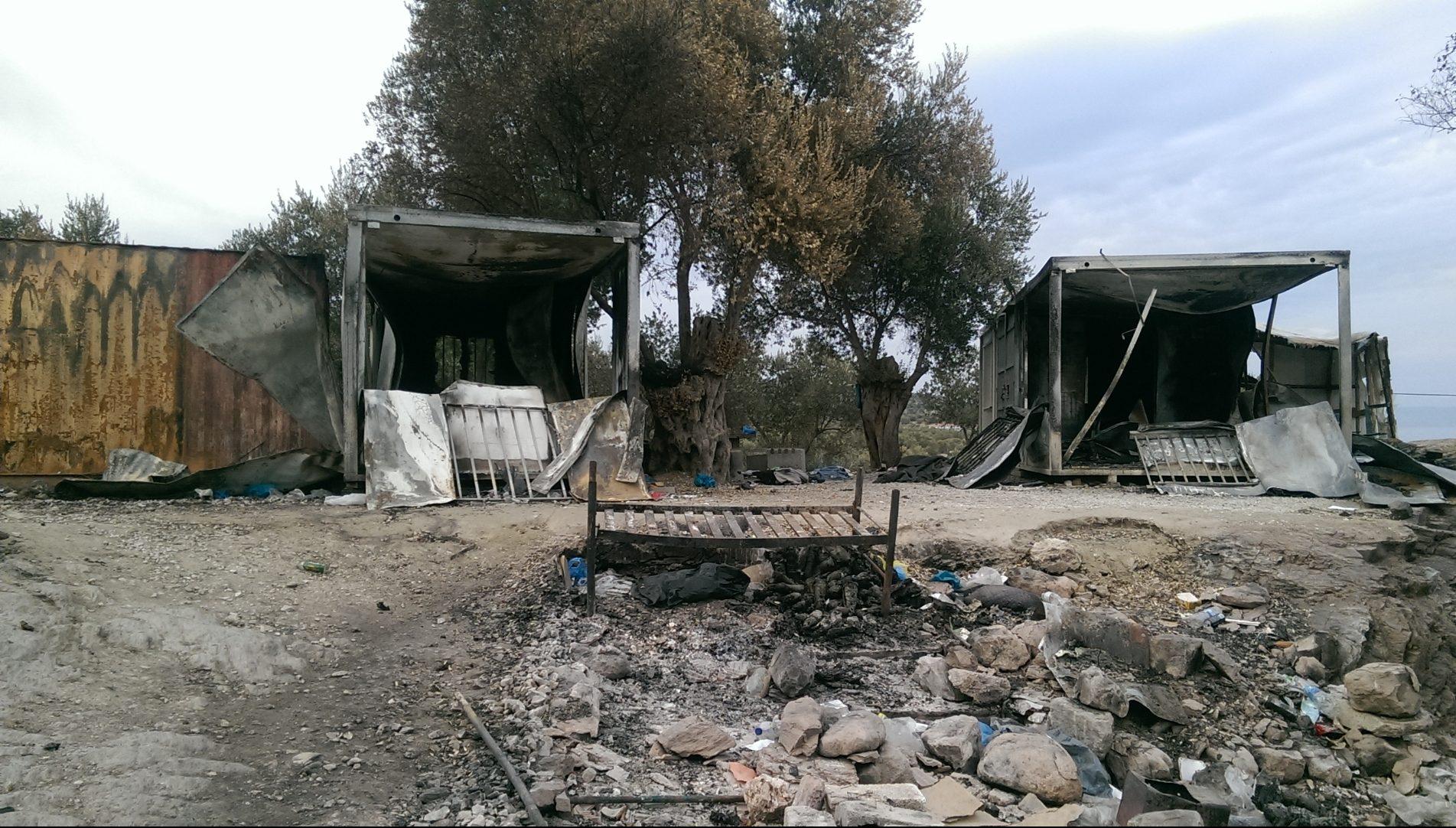 2. Bild: ausgebrannte Iso-Boxen, mit einem Bettgestell, das die Flammen überstand und zuvor ein Geschenk war, das nicht allen Menschen im Lager zuteil war.