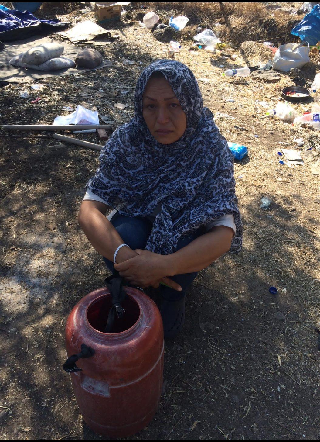 6. Bild: Frau sitzt vor einem Plastikbehältnis auf dem Erdboden. Im Hintergrund ein Notlager.