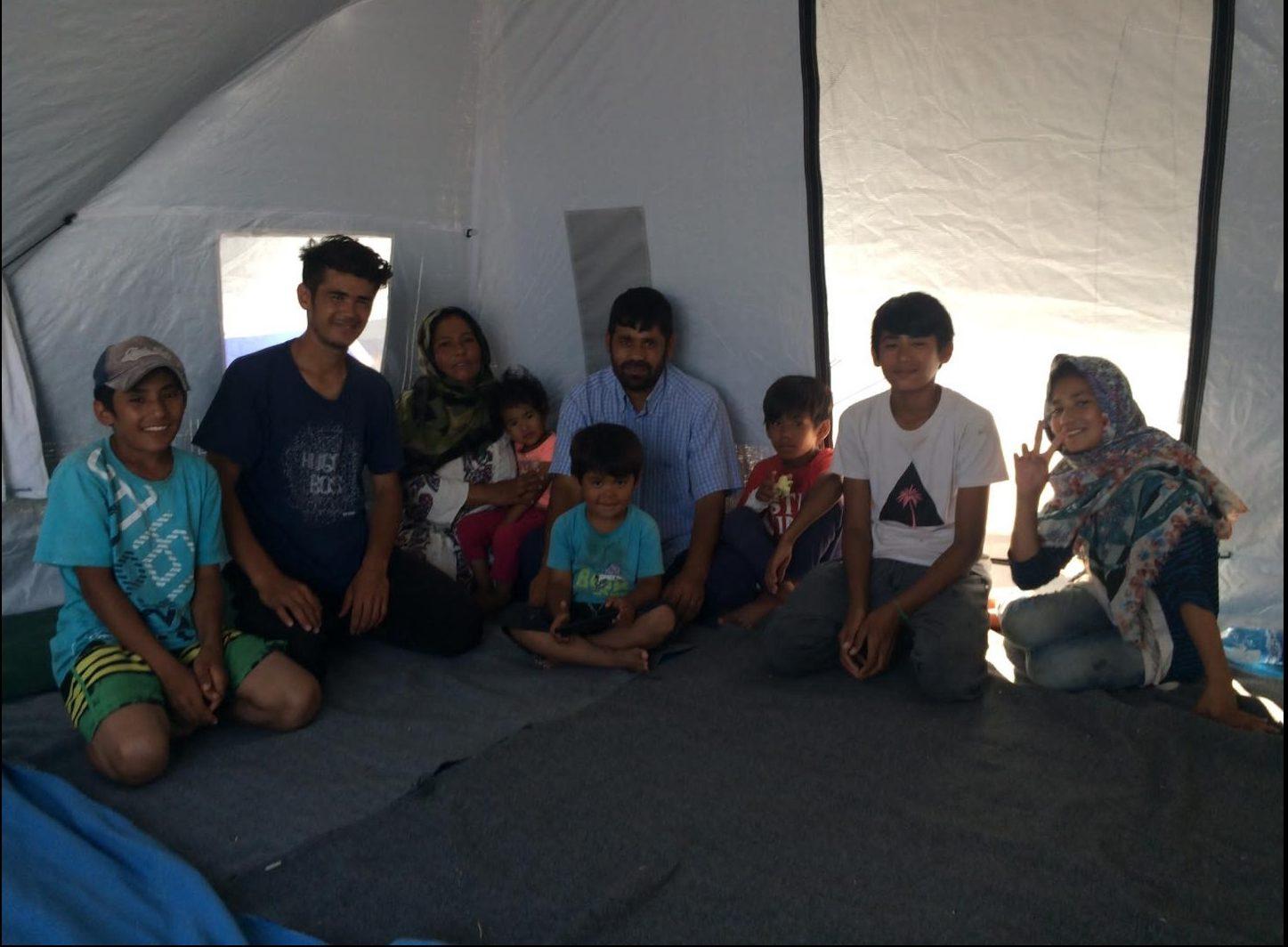 8. Bild: 9-köpfige Familie im Zelt. Die Personen lächeln.